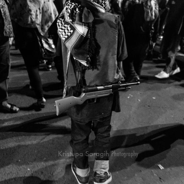 Anak-anak menyandang atribut mainan menyerupai senapan di pawai Malam Takbiran 1435H di Yogyakarta. Foto: Kristupa Saragih